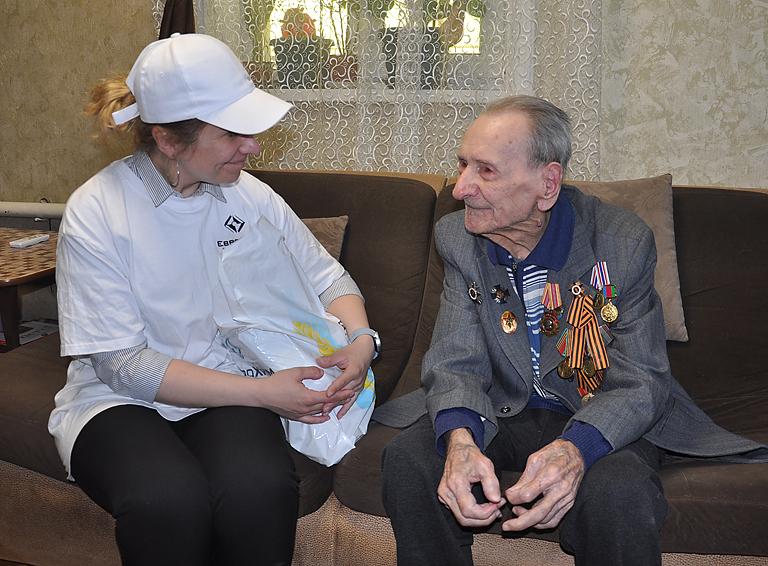 Главный специалист отдела по связи с общественностью «ЕвроХим-БМУ» Татьяна Мирошникова передаёт подарок ветерану Василию Акимову