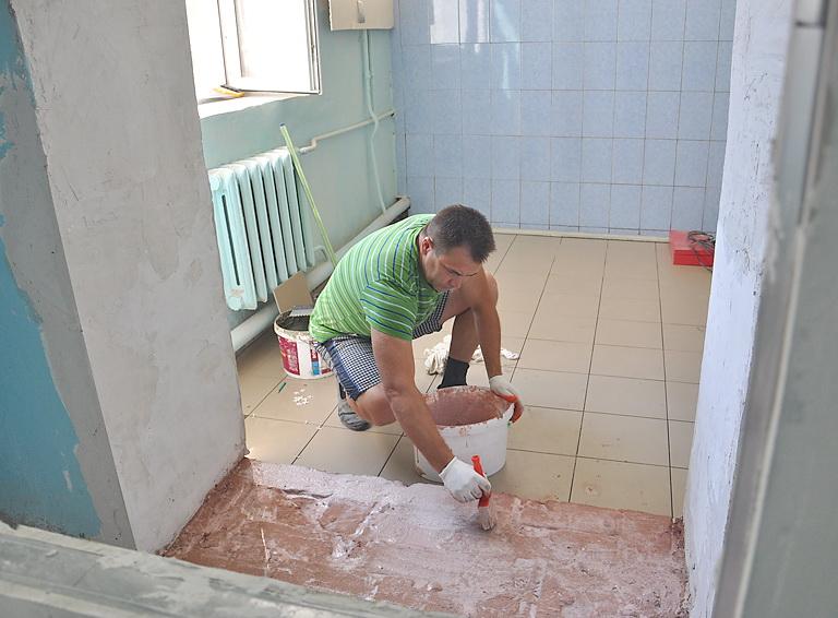 Учитель физкультуры школы №68 Анатолий Недобугин заканчивает работы с напольным покрытием