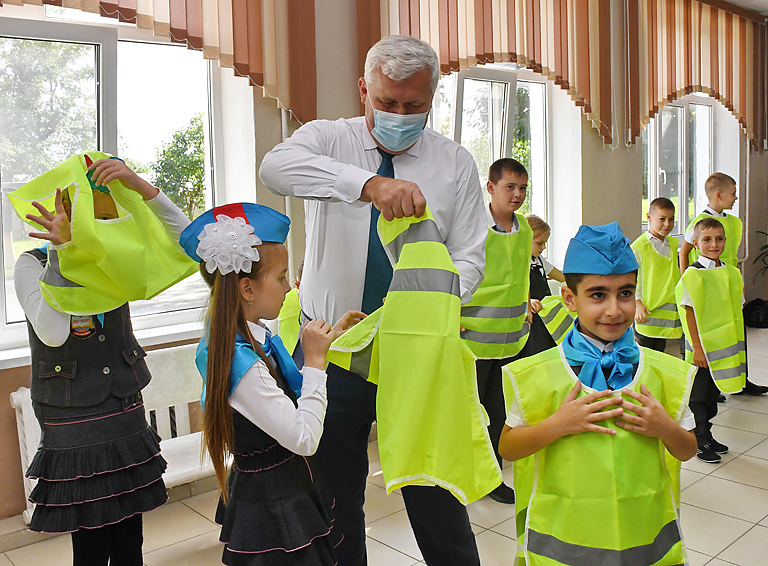 Глава района Александр Шаповалов помогает школьнице правильно надеть жилет  и напоминает о необходимости носить его в тёмное время суток